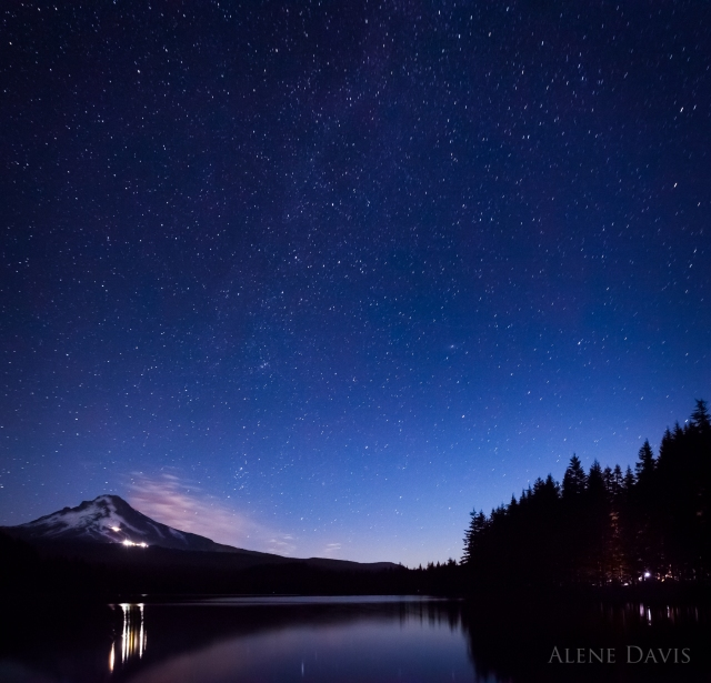 Campers light up the forest as evening falls and the stars come out over Mt. Hood at Trillium Lake, Oregon.