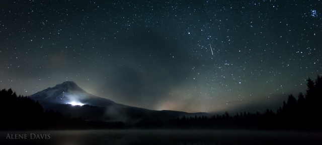 A meteor in the sky over a foggy Trillium Lake, with Mt. Hood in the background. Timberline lodge glows.