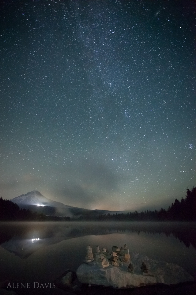 A rock cairn on the shore of Trillium Lake, with fog across the lake.